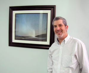 Dr. Israel poses before his winning image, framed and displayed at his practice.